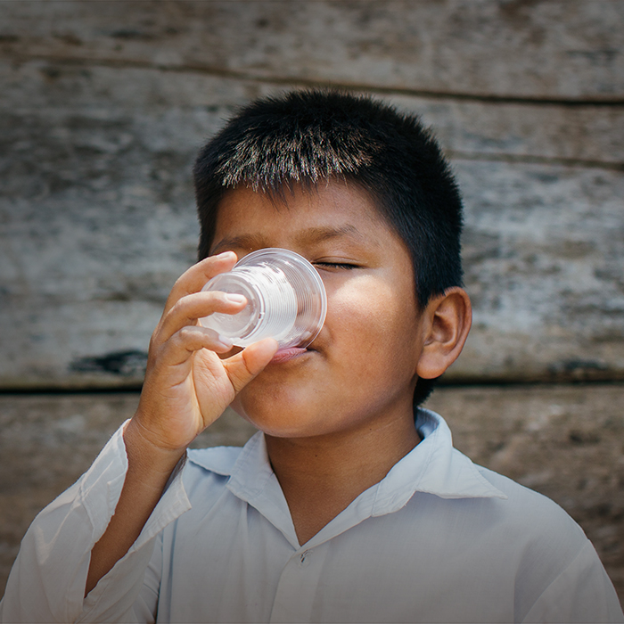 young boy drinking water from a cup