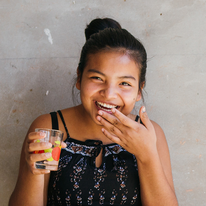 young girl drinking water and laughing
