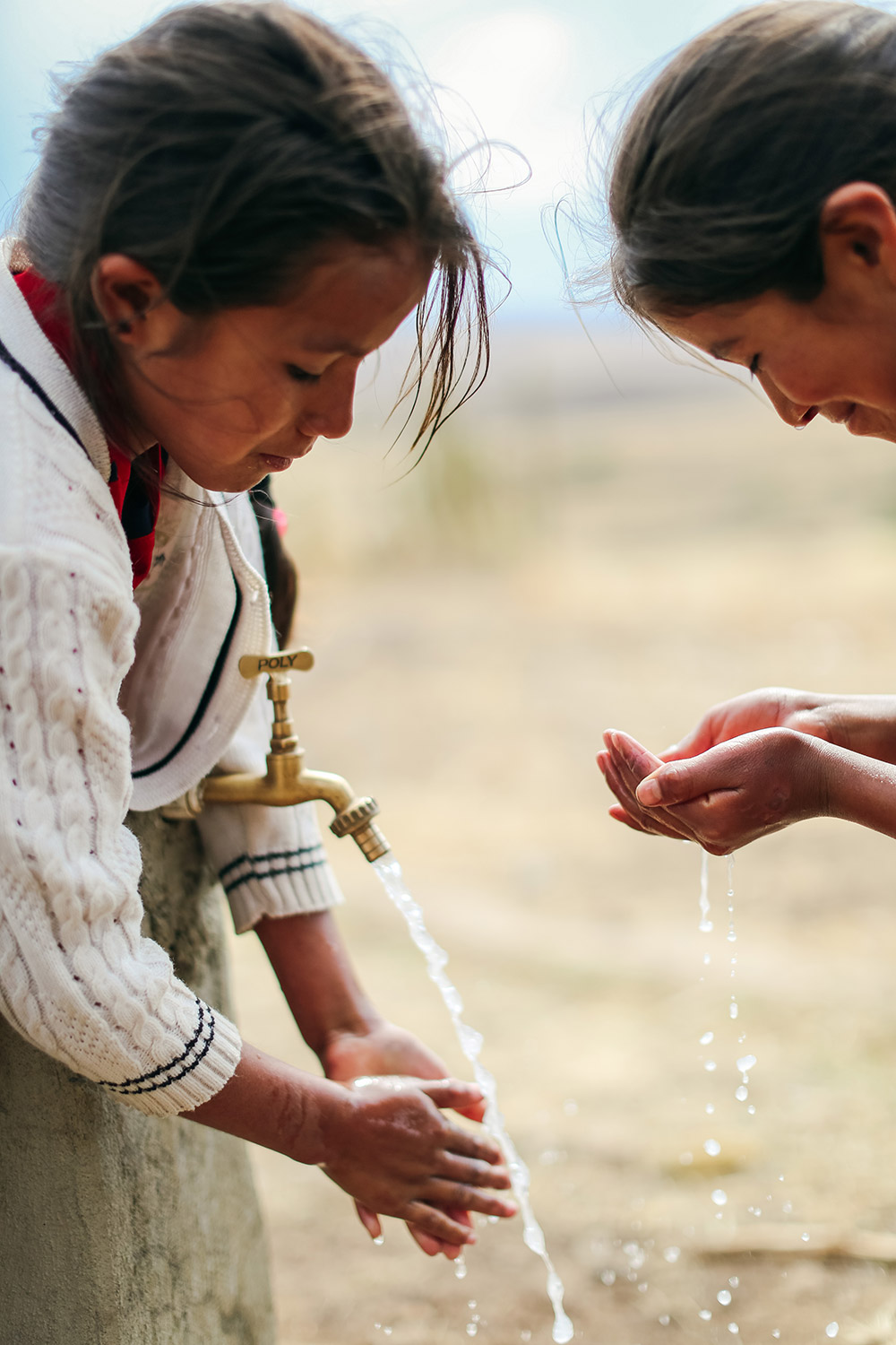 two girls washing their hands outside at a faucet | Clean Water in Bolivia | Where We Work | Water For People