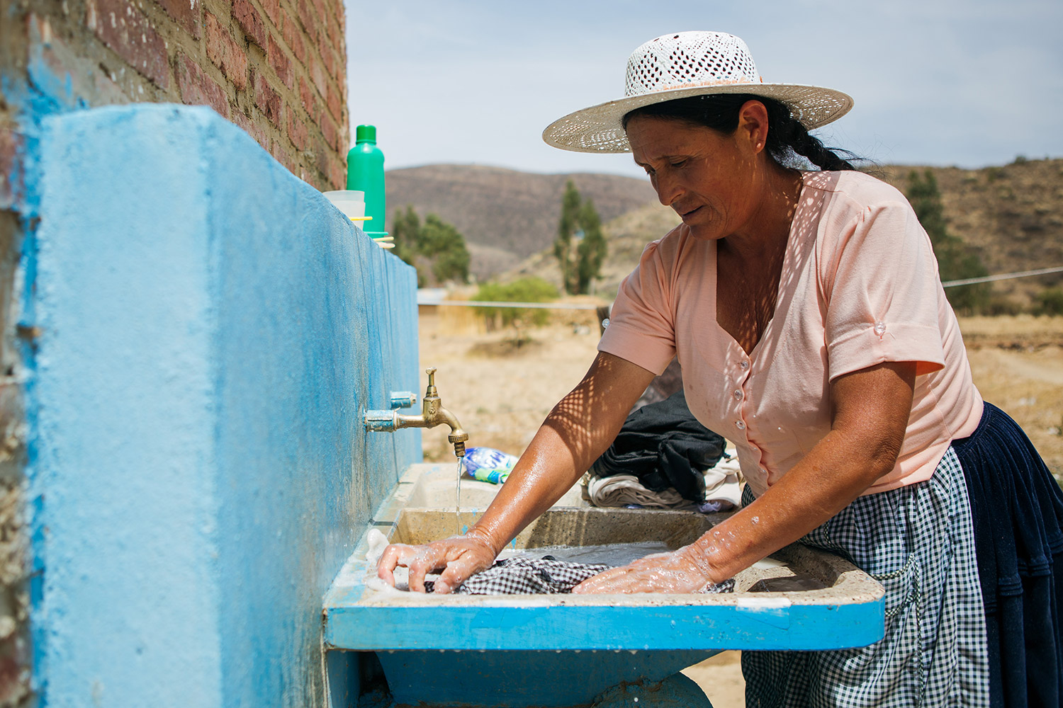 woman washing clothes in outdoor sink | Clean Water in Bolivia | Where We Work | Water For People