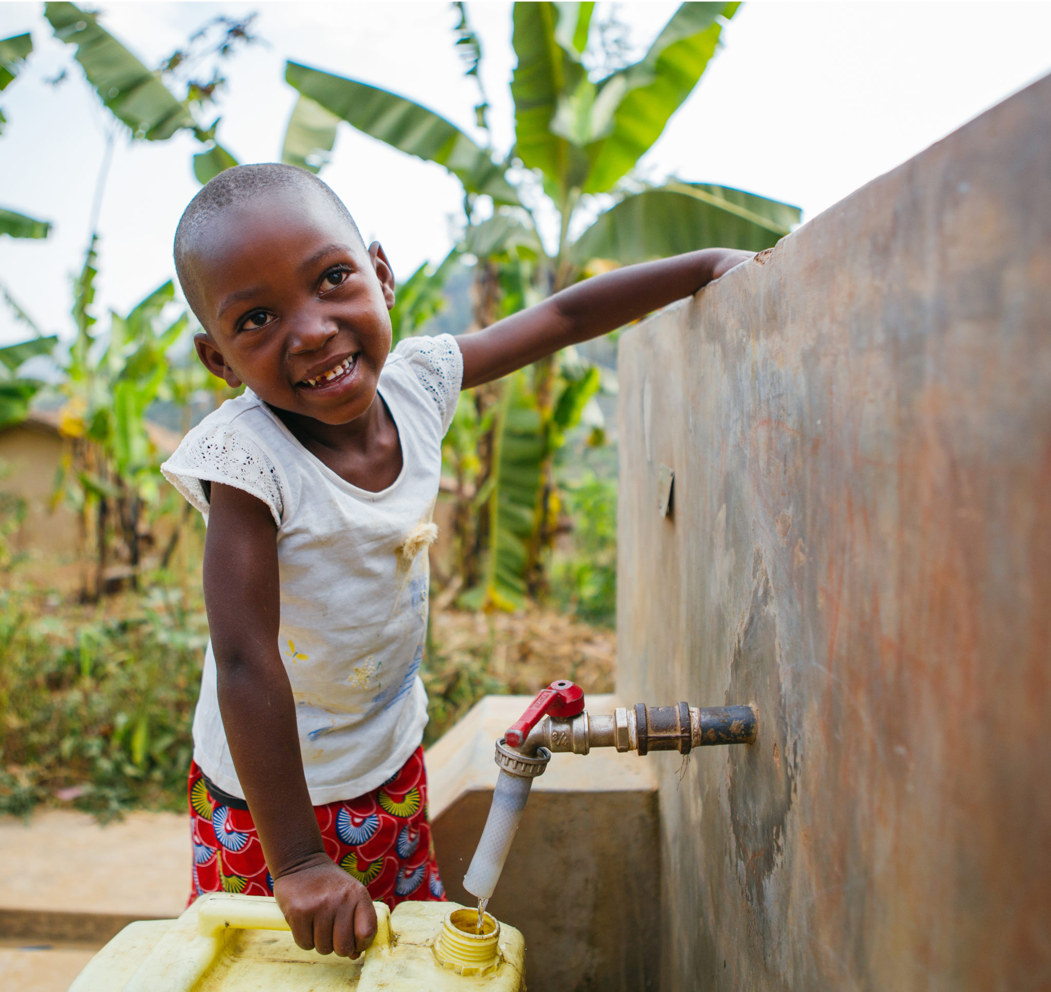 happy child filling up water jug | The Progress, Milestones & Stats | Water For People
