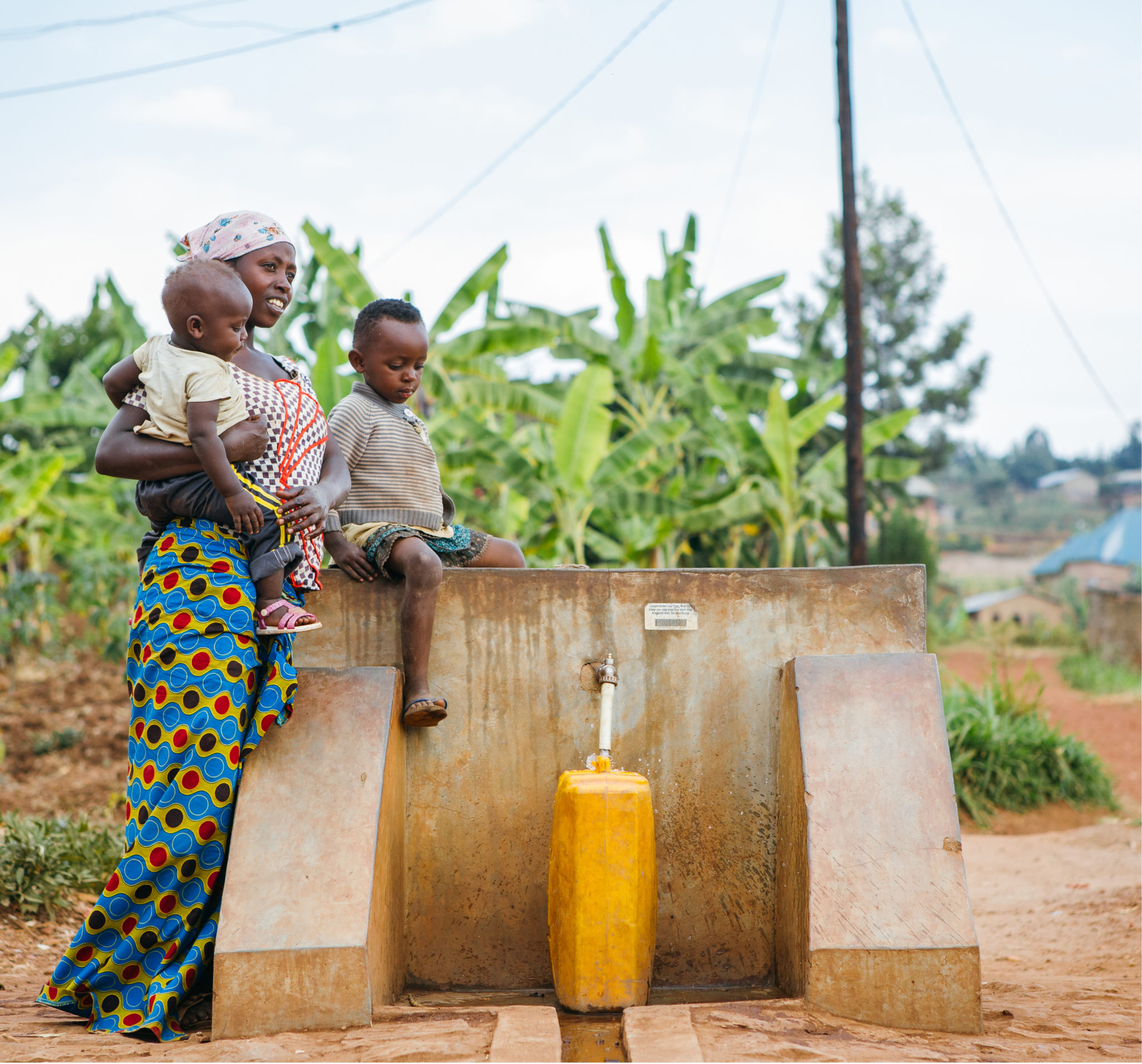 mother and children filling up water jug | Fundraise for Water | Get Involved | Water For People